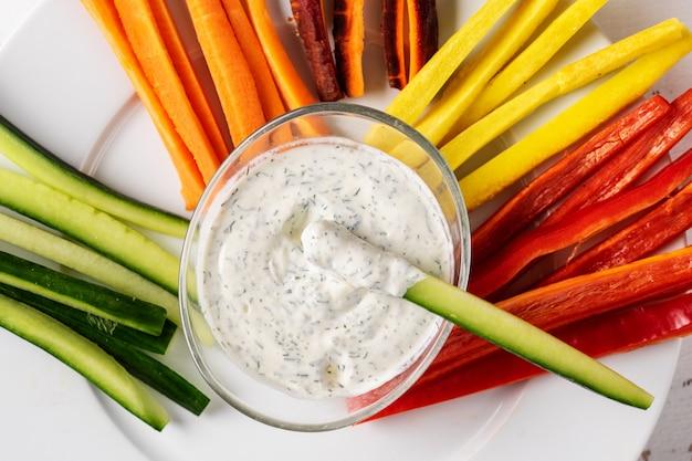 Gros plan d'une trempette à la crème avec des bâtonnets de légumes coroful.
