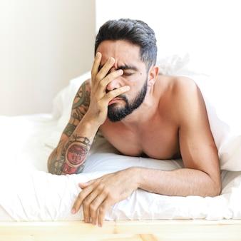 Gros plan, triste, jeune homme, coucher lit