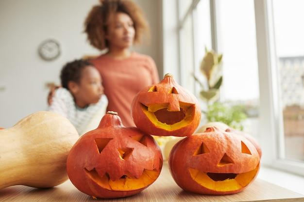 Gros plan de trois citrouilles orange préparées pour la fête d'halloween familiale moderne à la maison, copiez l'espace