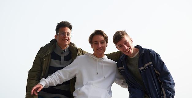 Un gros plan de trois jeunes amis caucasiens et hispaniques traînant dehors
