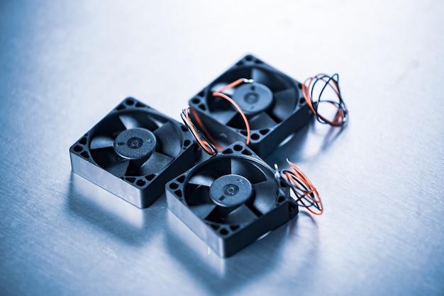 Gros plan sur trois petits refroidisseurs d'ordinateurs avec des fils posés sur une table sur une table grise. concept d'usine de pièces d'ordinateur.