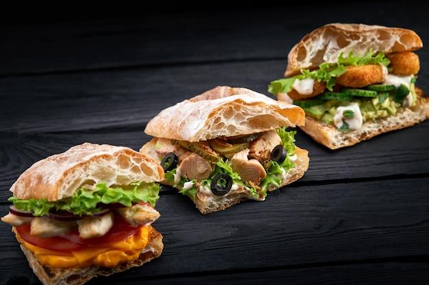 Gros plan trois sandwichs appétissants différents ou des hamburgers sur une surface en bois