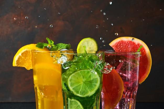 Gros plan trois verres à cocktail sur une table en pierre noire avec des éclaboussures d'eau sur une surface sombre