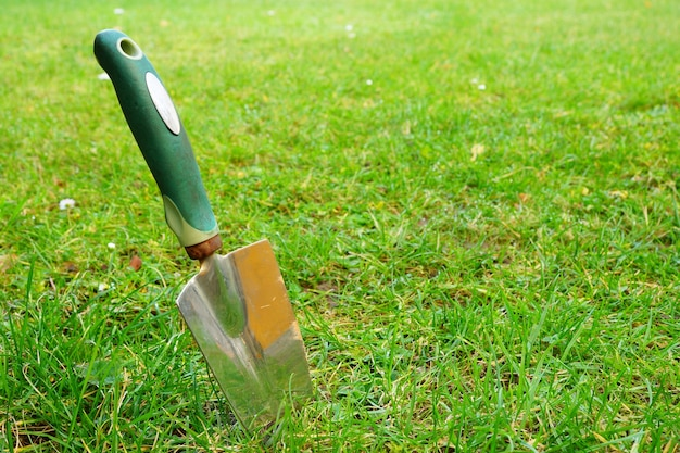 Gros plan d'une truelle à main sur l'herbe verte