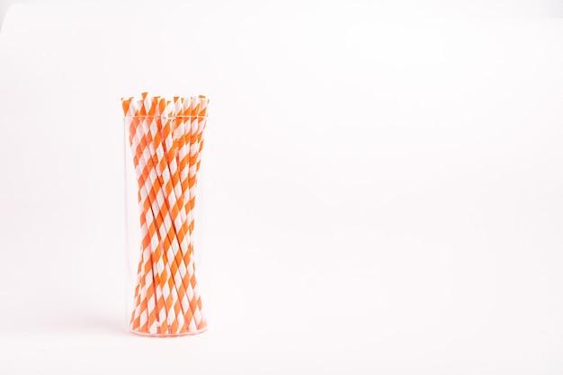 Gros plan sur des tubes à boire à rayures rouges et blanches dans un verre isolé sur une surface blanche
