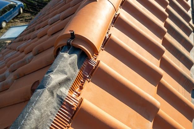 Gros plan de tuiles faîtières en céramique jaune sur le toit d'un immeuble résidentiel en construction.