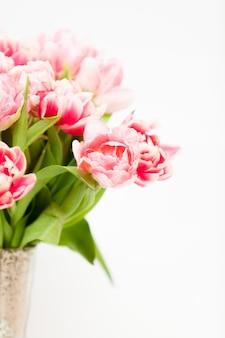 Gros plan de tulipes roses fraîches dans un vase contre blanc
