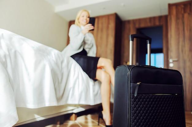 Gros plan de valise dans la chambre d'hôtel. femme d'affaires assise sur le lit et à l'aide d'un téléphone intelligent. elle est au symposium.