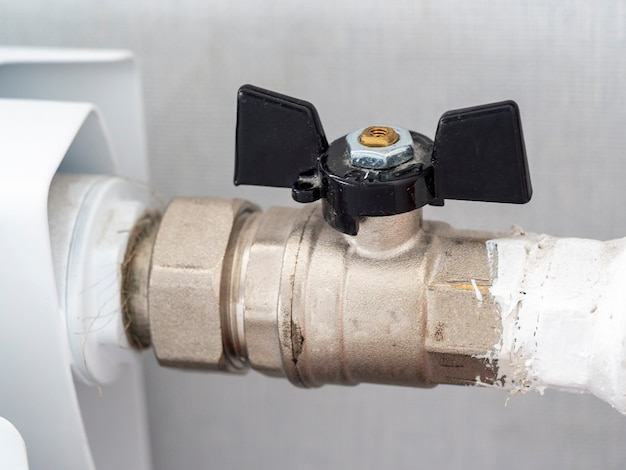 Gros plan sur la vanne de la batterie de chauffage domestique. régulation du débit et de la température dans la pièce