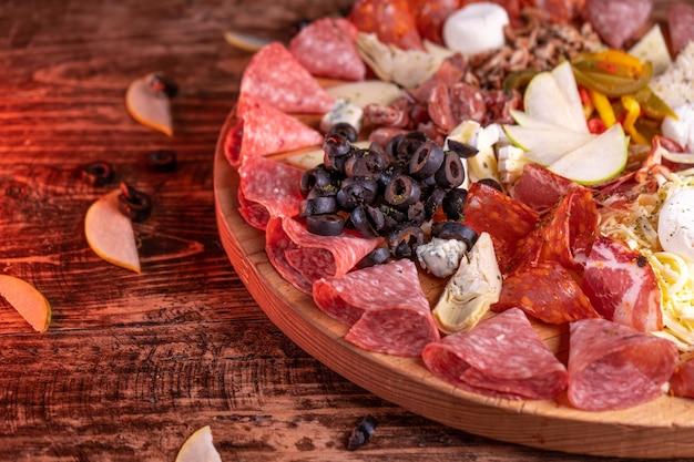 Gros plan d'une variété d'assortiment de viande sur une surface en bois