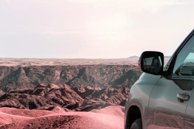 Gros plan d'un véhicule dans le sable devant une falaise. vallée de la lune. afrique. namibie