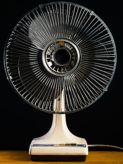 Gros plan d'un ventilateur de bureau blanc sur une table en bois