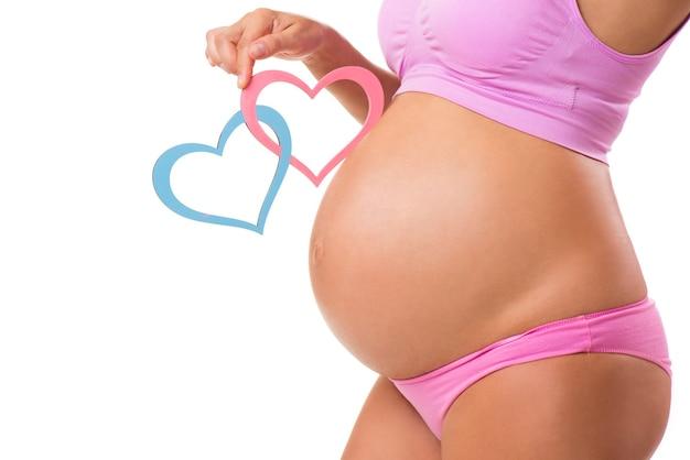 Gros plan d'un ventre de femme enceinte avec des coeurs roses et bleus devinez le sexe du bébé fille garçon ou jumeaux