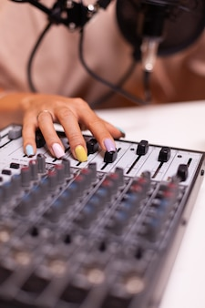 Gros plan sur la vérification du son à l'aide de la table de mixage pendant le podcast