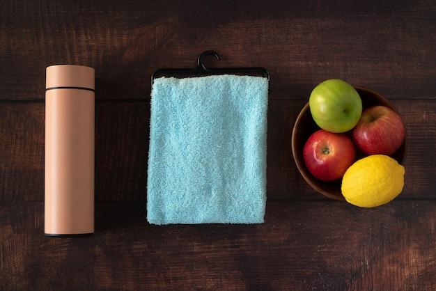 Gros plan vérifier tapis de yoga en tissu fruits et bouteilles d'eau placés sur un vieux fond en bois