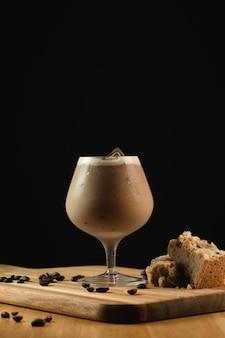 Gros plan d'un verre à cappuccino de glace sur une plaque en bois avec des décorations sur fond noir