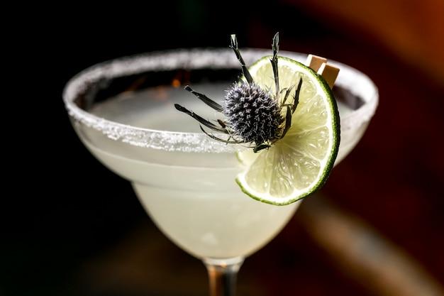 Gros plan d'un verre à cocktail garni de sel et de citron vert