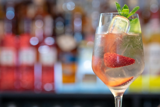 Gros plan d'un verre de cocktail glacé avec des fraises et du concombre sur un comptoir de bar