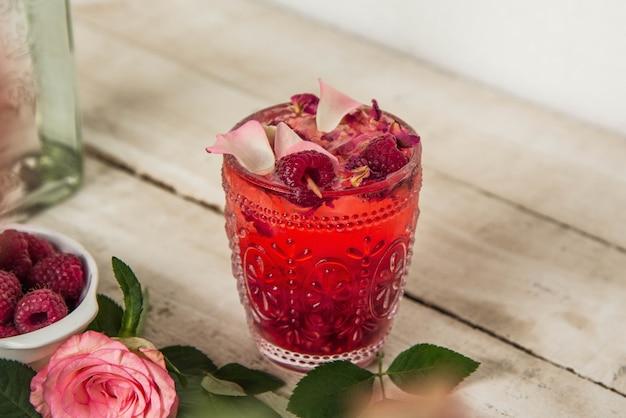 Gros plan d'un verre avec de la limonade aux framboises avec des fleurs séchées