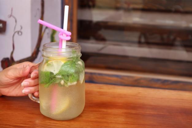Gros plan un verre de limonade glacée alléchante dans la main de la femme avec mise au point sélective