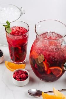 Gros plan sur verre et pichet de limonade aux framboises fraîches à la menthe et orange