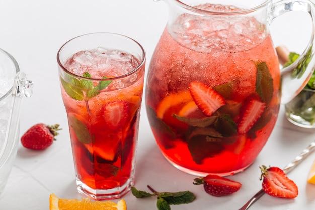Gros plan sur verre et pichet de limonade fraise rouge fraîche et fraîche à la menthe et orange