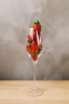 Gros plan d'un verre plein de fraises entières devant un mur gris