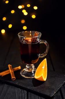Gros plan verre de vin chaud à l'orange et à la cannelle sur fond noir foncé, lumières de noël, grand bokeh jaune