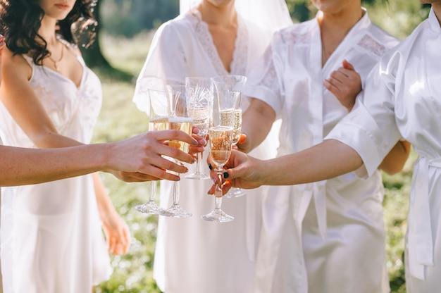 Gros plan de verres de champagne entre les mains des demoiselles d'honneur et des mariées vêtues de peignoirs de soie blanc clair dans la cour du jardin. matin de la mariée.