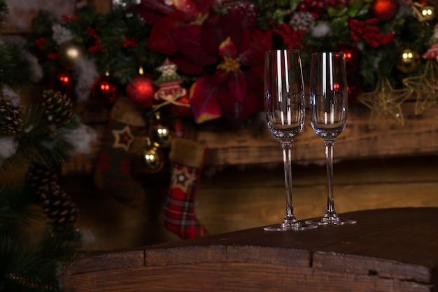 Gros plan sur des verres à flûte à champagne vides debout sur une plate-forme en bois avec des décorations de noël à l'arrière-plan.