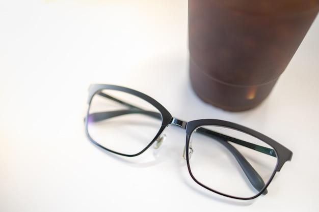 Gros plan de verres de lecture avec une tasse en plastique de café noir glacé sur le tableau blanc.