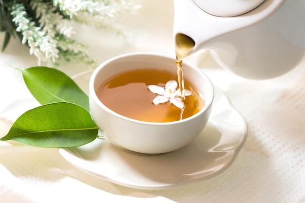 Gros plan versant le thé au jasmin chaud dans une tasse de thé blanc, concept de temps de cérémonie du thé