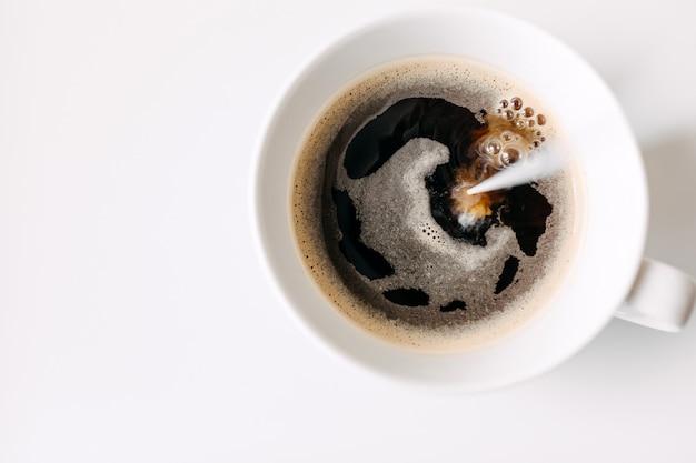 Gros plan de verser le lait dans une tasse de café noir sur tableau blanc