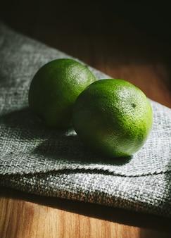 Gros plan vertical à angle élevé de deux limes entières sur une table en bois