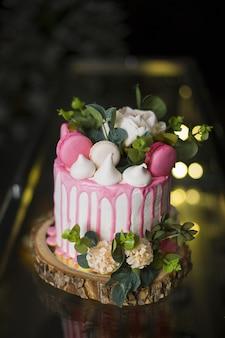 Gros plan vertical d'un beau gâteau avec des fleurs et des macarons