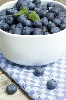 Gros plan vertical de bleuets frais dans un bol blanc