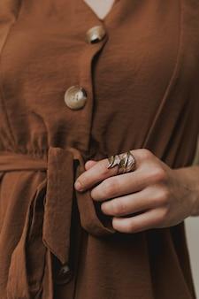 Gros plan vertical d'une femme portant une robe marron et un anneau en forme de feuille métallique
