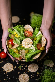 Gros plan vertical d'une personne tenant un bol de salade avec des craquelins et des légumes sous les lumières