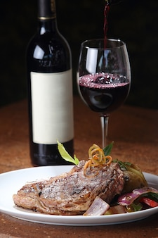 Gros plan vertical d'un steak en t fraîchement grillé et un verre de vin en arrière-plan