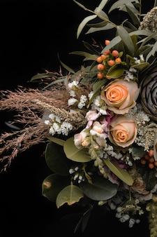 Gros plan vertical tiré d'un luxueux bouquet de roses orange et marron sur fond noir