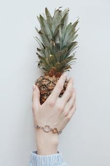 Gros plan vertical tiré d'une main féminine avec un joli bracelet doré tenant un ananas entier