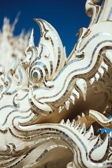 Gros plan vertical tiré d'une statue de dragon dans le temple blanc de chiang rai, thaïlande
