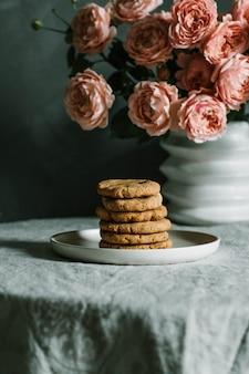 Gros plan vertical tourné de cookies au four empilés sur une plaque près de roses roses dans un vase sur une table