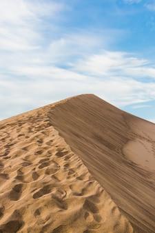 Gros plan vertical tourné d'un désert de sable beige sous un ciel bleu clair