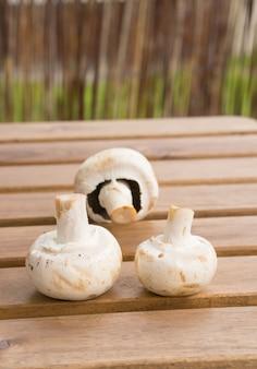 Gros plan vertical de trois champignons frais sur une surface en bois