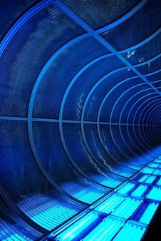 Gros plan vertical d'un tunnel transparent moderne en forme de tuyau avec des lumières bleues sur le fond