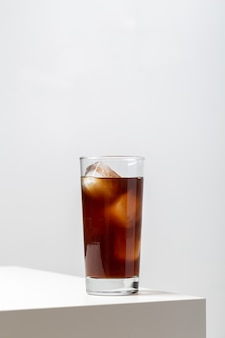Gros plan vertical d'un verre de thé glacé sur la table sous les lumières sur un fond blanc