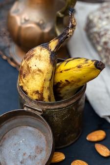 Gros plan vertical de vieilles bananes dans une boîte rouillée
