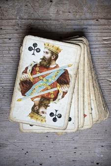 Gros plan vertical de vieilles cartes à jouer patinées sur une table en bois