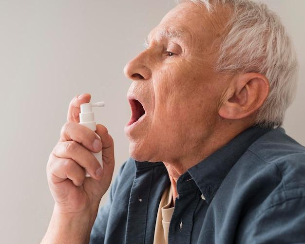 Gros plan vieil homme à l'aide de spray oral